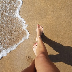 beautiful tanned legs of a girl on the golden sand. Rest on the ocean. Sand beach