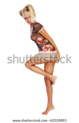 Beautiful tanned slim young sexy woman in mini dress dancing on white background