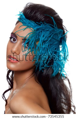 beautiful tanned woman with long black hair in fashion hairstyle and a blue feather covering her face.