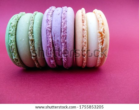 Beautiful tasty macaroon cakes lie on a bright pink background. Orange, violet, green macaroons on a bright substrate. Background with macaroons. Tasty sweets on a dessert. Macro of three macaroons.