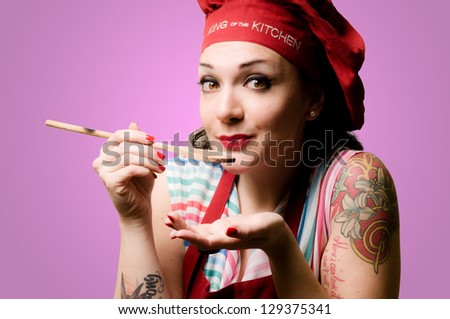 beautiful tattooed pinup cook girl on pink background