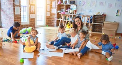 Beautiful teacher and group of toddlers sitting on the floor drawing using paper and pencil around lots of toys at kindergarten