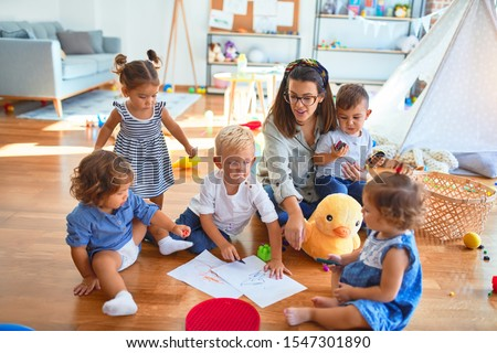 Beautiful teacher and group of toddlers sitting on the floor drawing using paper and pencil around lots of toys at kindergarten ストックフォト ©