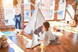 Beautiful teacher and toddler playing inside tipi around lots of toys at kindergarten