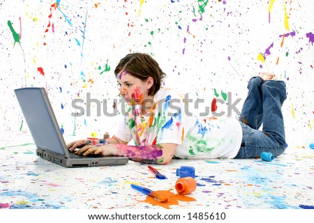 Beautiful teen girl covered in paint with laptop laying on floor