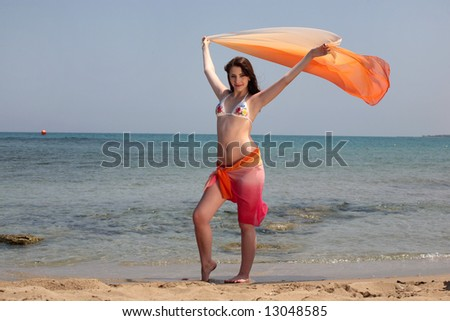 stock photo beautiful teen girl in swimwear holding up a wrap standing on the beach 13048585 stock photo : beautiful teen girl in swimwear holding up a wrap standing on ...