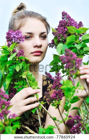 stock photo : Beautiful teen girl smelling lilac blossoms