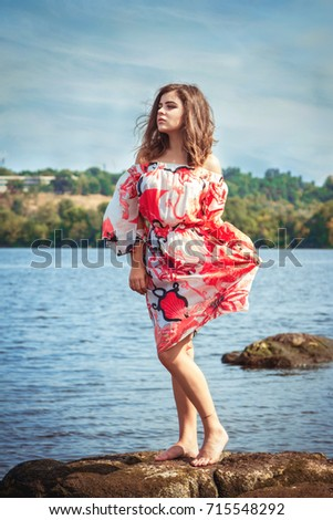 e1bbf6bbf14 Beautiful teen girl, standing barefoot on a stone cliff in river water on a  sunny