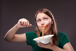 Beautiful teen girl thinking and eating pasta with ketchup on her face