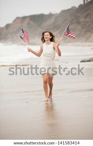 Beautiful Teen Girl with American flags walking on the Beach in Malibu