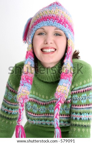 ... teen girl with dazzling smile in green sweater and crazy winter hat