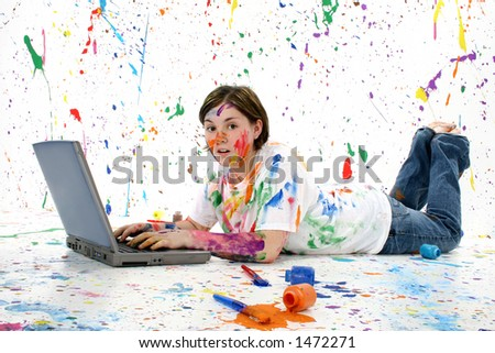 Beautiful teen girl with surprised look covered in paint with laptop