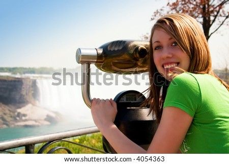 Beautiful teen looking back from her view from the stationary binoculars at a scenic overlook.