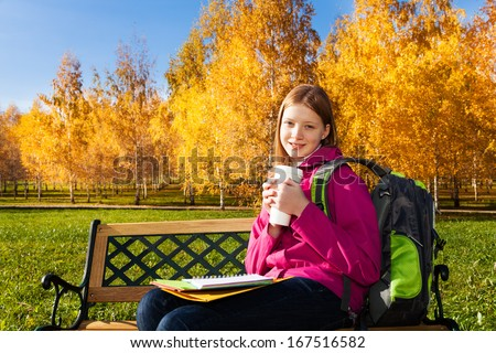 Beautiful teen 14 years old school girl sitting on the bench in autumn park wearing backpack with coffee