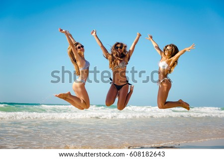 Beautiful teenage friends jumping on the beach