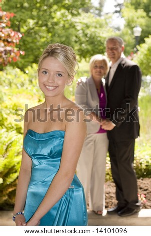 Beautiful teenage girl dressed up for the prom, parents in the background. - stock photo
