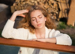 Beautiful teenage girl in a white cardigan dreamily closed her eyes, in the yard in nature. Posing alone. Harmony with nature, relaxation, dreams, fantasies. Beige monochrome