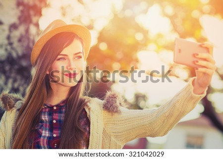 Beautiful teenage girl in beige hat and sweater taking a selfie on smartphone outdoors in park on sunny autumn day. Cute young woman photographing herself. Retouched, horizontal, vibrant colors.