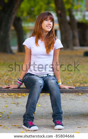 Beautiful teenage girl in fashionable warn out jeans, t-shirt and sneakers smiles while watching the nature on the nice autumn day.