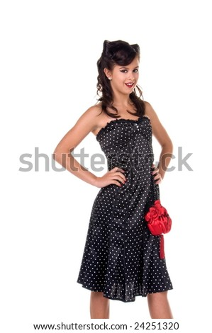 Beautiful teenage girl in 1950's rockabilly fashion polka dot dress, hair and red clutch purse