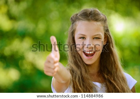 Beautiful teenage girl in white blouse lifts thumb upwards, against green of summer park.