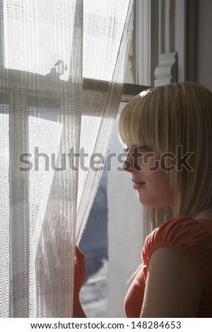 Beautiful teenage girl looking through window at home