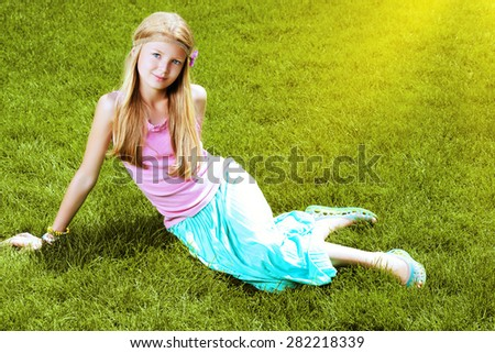 Beautiful teenage girl lying on a green lawn in the park. Harmony. Holiday.