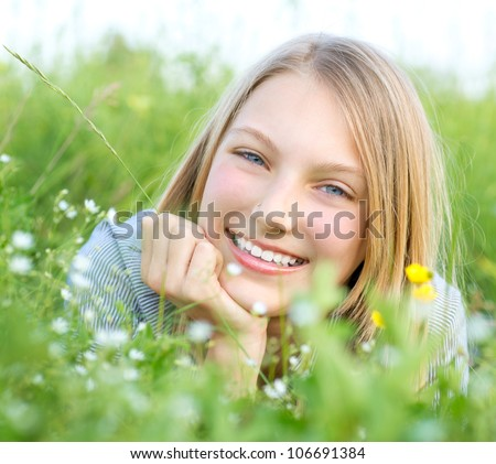 Beautiful Teenage Girl lying on Meadow of Flowers and Green Grass.. Happy and Smiling. - stock photo