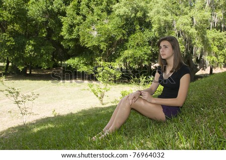 Beautiful teenage girl outdoors sitting and day dreaming