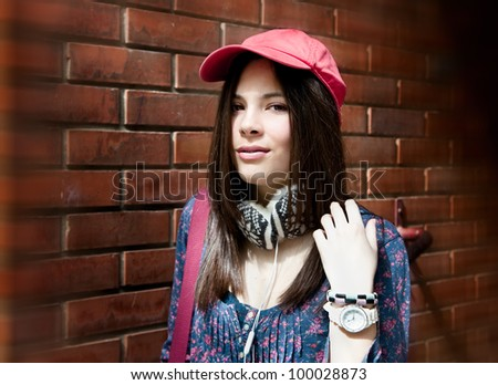 Beautiful teenage girl posing over red brick wall - stock photo