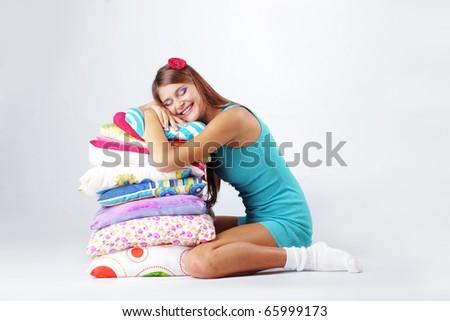 Beautiful teenage girl resting on pillows studio shot