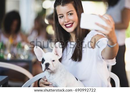 Beautiful teenage girl taking selfie photo with her french bulldog puppy.