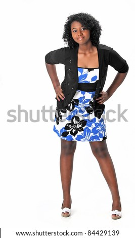 Beautiful teenage girl wearing a dress, sweater and heels is posing on a white background with space for copy.