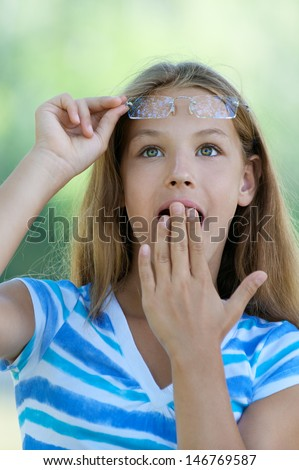 Beautiful teenage girl with her hand covers mouth in amazement, against green of summer park.