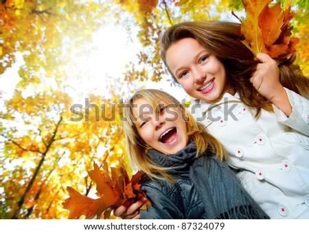 Beautiful Teenage Girls Having Fun in Autumn Park .Outdoor