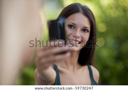 Beautiful teenage girls photographing with camera phone - stock photo