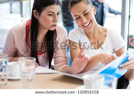 beautiful teenage student discussing her studies with a friend during their break.