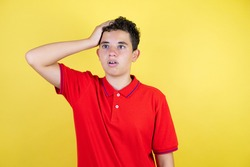 Beautiful teenager boy over isolated yellow background putting one hand on her head surprised like she had forgotten something