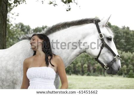 beautiful teenager day dreaming against a horse in field