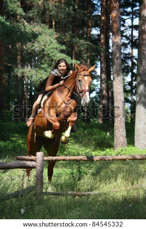 Beautiful teenager girl in dress riding chestnut horse and jumping over wooden fence