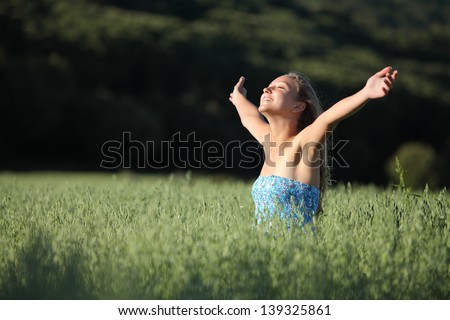Beautiful teenager girl laughing happy with raised arms in a green meadow with a dark background
