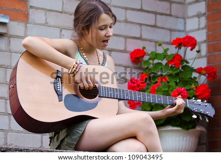 Beautiful teenager girl playing the guitar and singing near flowers outdoors