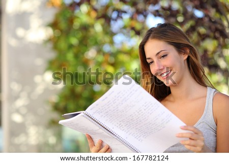 Beautiful teenager girl studying reading a notebook outdoor with a green background