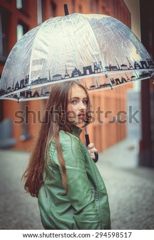 Beautiful teenager girl under the umbrella at a rainy day