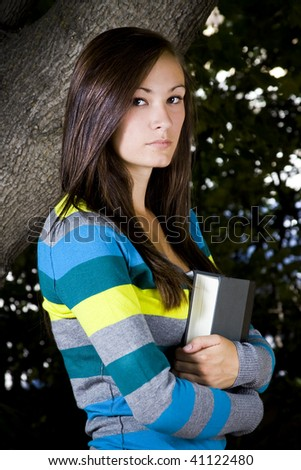 Beautiful Teenager holding a book with Leaves in the Background