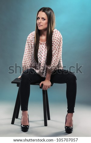 beautiful teenager sitting on a stool in blue light wearing black jeans