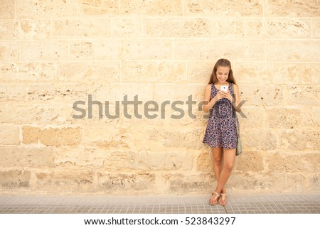 Beautiful teenager student girl using smart phone leaning against plain golden stone texture wall in college campus, networking and smiling, outdoors. Adolescent technology lifestyle, school exterior.