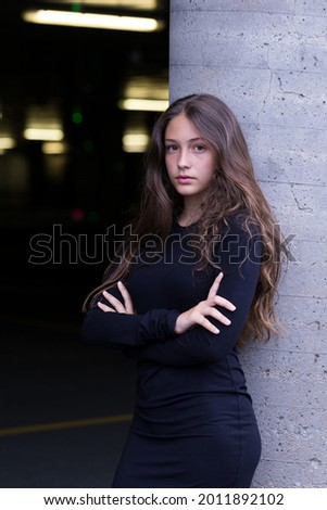 Beautiful teenager with long hair in tight black dress leaning on concrete column waiting near the entrance of an interior parking with arms crossed Stock photo ©