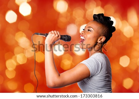 Beautiful teenager woman singing karaoke concert artist holding microphone on red orange blurred lights background