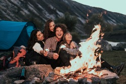 Beautiful teens with large white smile have a good time together at camping , playing with some lightning sparklers